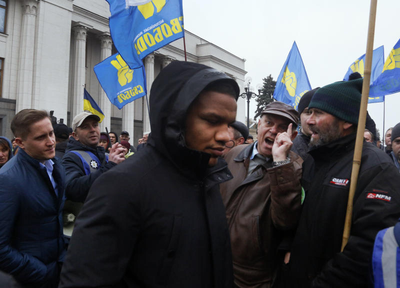 Zhan Beleniuk, world wrestling champion and lawmaker of President Volodymyr Zelenskiy's 'Servant of the People' party, center, passes through the crowd of angry protesters outside the parliament building after a parliament session in Kyiv, Ukraine, Wednesday, Nov. 13, 2019. After an hours-long debate in parliament in which tempers flared, the majority of Ukrainian lawmakers passed a bill lifting the ban on buying and selling farmland. It received 240 votes, requiring 226 to pass. (AP Photo/Efrem Lukatsky)