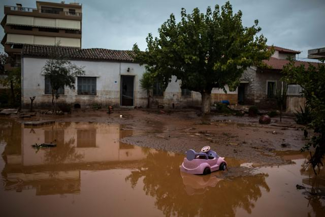 A toy car is seen in a flooded street next to a damaged house in the town of Mandra.