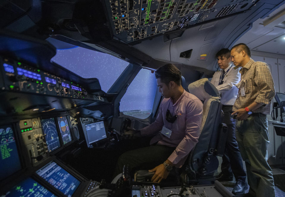 Pilot Akarapol Apanant, center, explains to customers in a Boeing A380 flight simulator at the Thai Airways head office in Bangkok, Thailand on Oct. 3, 2020. The airline is selling time on its flight simulators to wannabe pilots while its catering division is serving meals in a flight-themed restaurant complete with airline seats and attentive cabin crew. The airline is trying to boost staff morale, polish its image and bring in a few pennies, even as it juggles preparing to resume international flights while devising a business reorganization plan. (AP Photo/Sakchai Lalit)