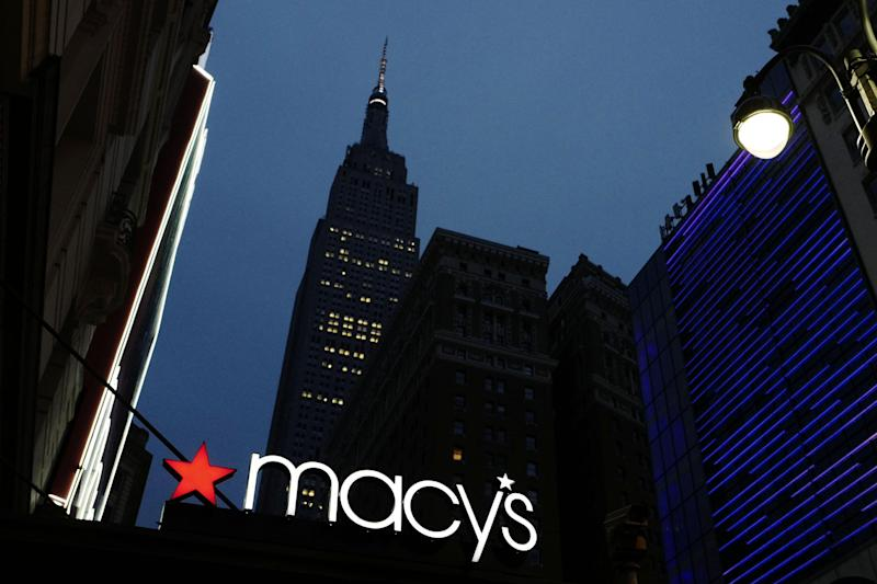 File- This Sept. 17, 2016, file photo shows a Macy's sign being illuminated on a store marquis, in New York. Macy's says it is eliminating more than 10,000 jobs and plans to move forward with 68 store closures after a disappointing holiday shopping season. The department store chain also lowered its full-year earnings forecast. (AP Photo/Mark Lennihan)
