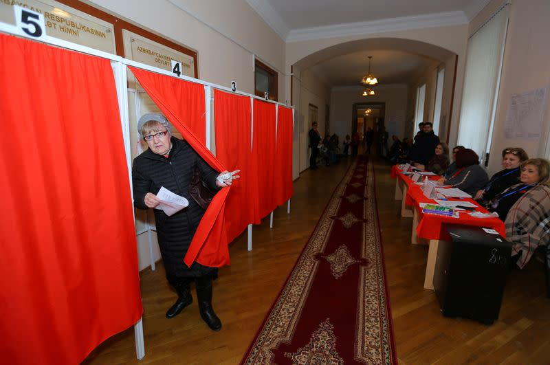 A woman attends voting at a polling station during a snap parliamentary election in Baku