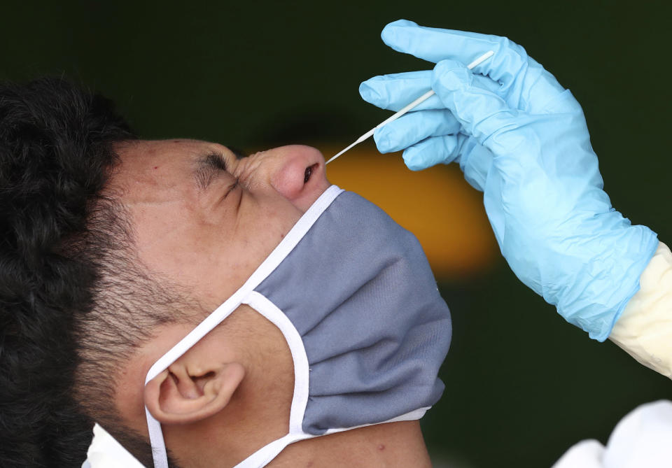 A man reacts as a health worker collects nasal swab samples from him during a mass test for the new coronavirus at a market in Jakarta, Indonesia, Thursday, June 25, 2020. (AP Photo/Tatan Syuflana)