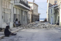 People walk past a destroyed house after an earthquake in the island of Samos on October 30, 2020. - A powerful earthquake hit Greece and Turkey on October 30, 2020, causing buildings to collapse and a sea surge that flooded streets in the Turkish resort city of Izmir. Greek public television said the quake also caused a mini-tsunami on the eastern Aegean Sea island of Samos, damaging buildings. The US Geological Survey said the 7.0 magnitude quake was registered 14 kilometres (8.6 miles) off the Greek town of Karlovasi on Samos. (Photo by STR / Eurokinissi / AFP) (Photo by STR/Eurokinissi/AFP via Getty Images)
