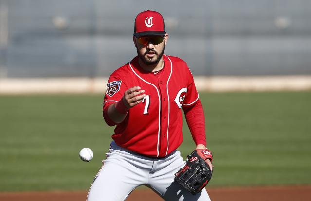 FILE - In this Feb. 20, 2018, file photo, Cincinnati Reds third baseman Eugenio Suarez flips a baseball away after fielding a grounder at the team's spring training facility in Goodyear, Ariz. Suarez and the Reds have agreed to a $66 million, seven-year contract, a deal that includes a team option for 2025 that if exercised would make the deal worth $79 million over eight years. (AP Photo/Ross D. Franklin, File)