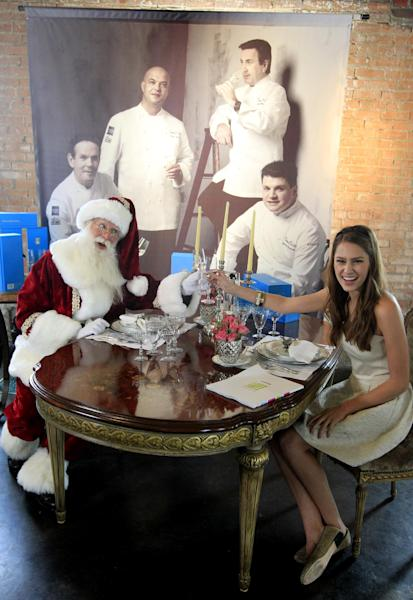 Brady White, portraying Santa Clause, left, and model Kit Johnston display the private dinner for 10 gift with four world renowned chefs preparing the meal during the unveiling of the Neiman Marcus 2012 Christmas Book in Dallas, Tuesday, Oct. 9, 2012. The meal that includes a Casa Dragones tequila tasting is priced for sale at $250,000. (AP Photo/LM Otero)