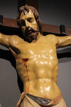 Sculpture of Christ on the cross showing arm hinges.