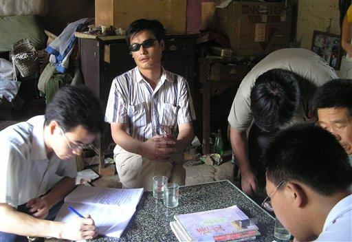 In this undated photo released by supporters of Chen Guangcheng, blind activist Chen Guangcheng, center, is seen in a village in China. Chen is due to go on trial Friday Aug. 18, 2006 in eastern China on criminal charges that his supporters claim were fabricated as retaliation for his activism. Supporters of a blind Chinese activist who documented forced abortions are being kept under house arrest as authorities prepare to put him on trial this week, activists said Thursday, Aug. 17, 2006. (AP Photo/Supporters of Chen Guangcheng, HO)