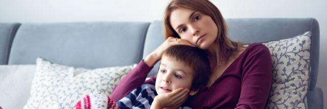 Mother holding son on the couch, looking worried.