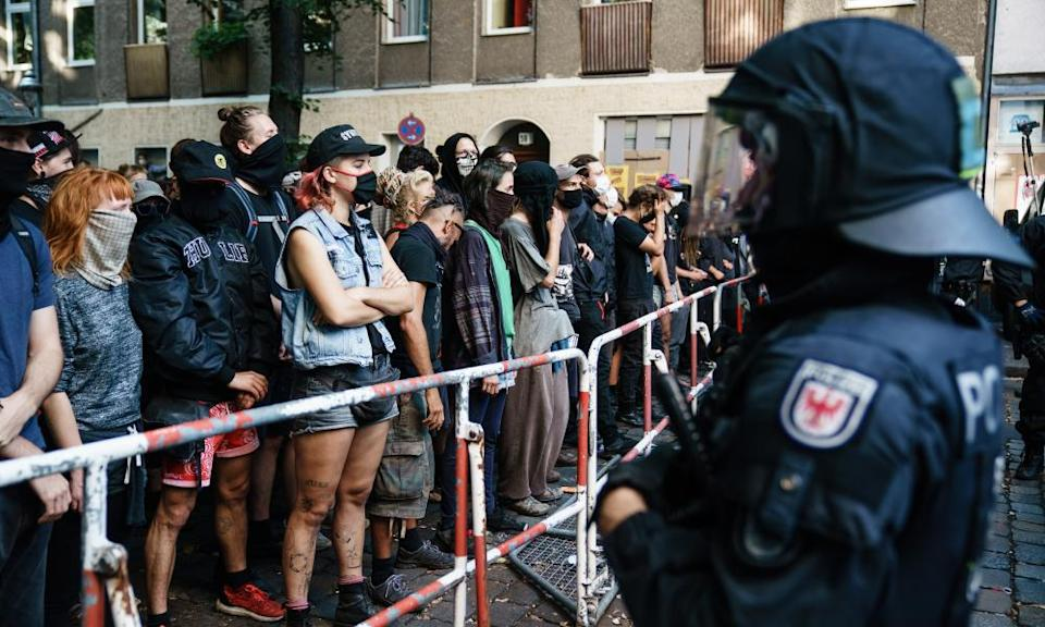 Demonstrators stand in front of a police line during the seizure of the bar