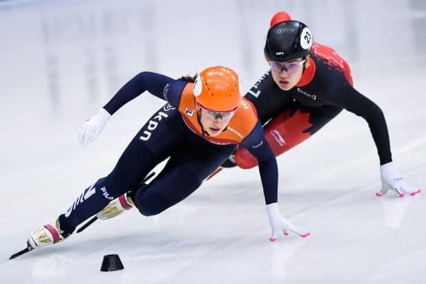 Canada's Courtney Sarault, shown at right in this 2020 file photo with Netherlands' Suzanne Schulting, captured bronze in the women's 1,000m final at the short track speed skating worlds on Sunday in Dordrecht, Netherlands.  (Jens Meyer/The Associated Press - image credit)
