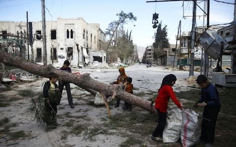 Children gather wood in the besieged town of Douma, Eastern Ghouta, in Damascus - Credit: Reuters