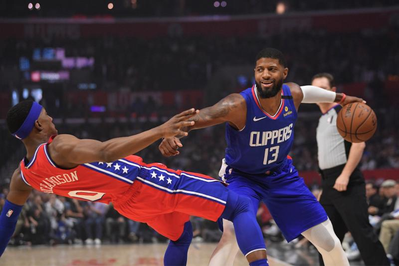 Philadelphia 76ers guard Josh Richardson, left, goes down as Los Angeles Clippers guard Paul George tries to drive past him during the first half of an NBA basketball game Sunday, Mar. 1, 2020, in Los Angeles. (AP Photo/Mark J. Terrill)