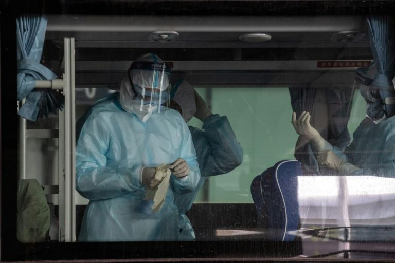 Health workers at Wuhan's international airport as a World Health Organization team arrives to investigate the origins of the Covid-19 pandemic