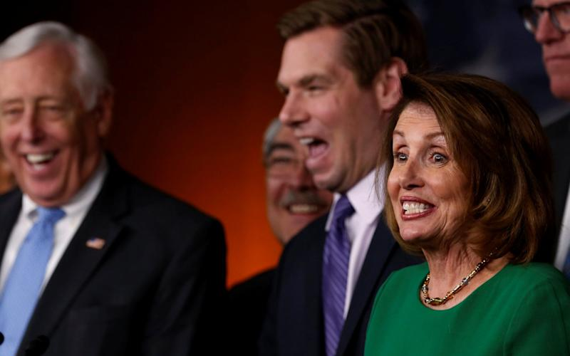 House Minority Leader Nancy Pelosi, flanked by two Democrat colleagues, laughs during a news conference on the Republicans' attempt to repeal the Obamacare health care legislation - Credit: Reuters