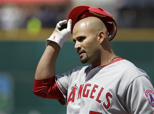 Los Angeles Angels' Albert Pujols takes off his batting helmet and heads back to the dugout after grounding out against the Cleveland Indians in the first inning of a baseball game in Cleveland, Sunday, April 29, 2012. (AP Photo/Amy Sancetta)