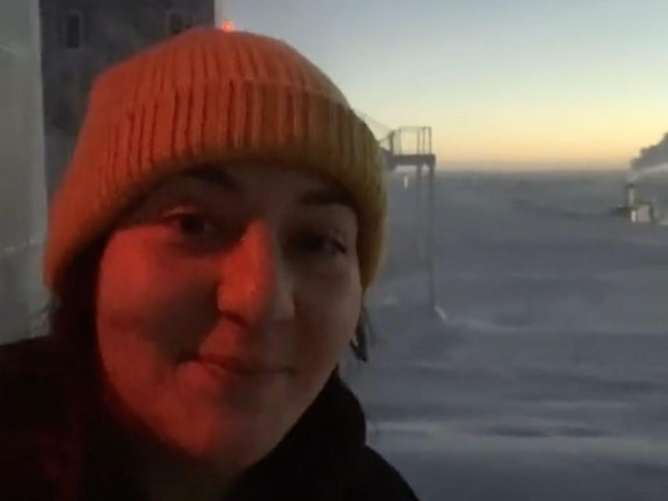 """Antoinette """"Toni"""" Traub standing just outside the Amundsen-Scott South Pole Station, behind her the sun is setting in the horizon."""
