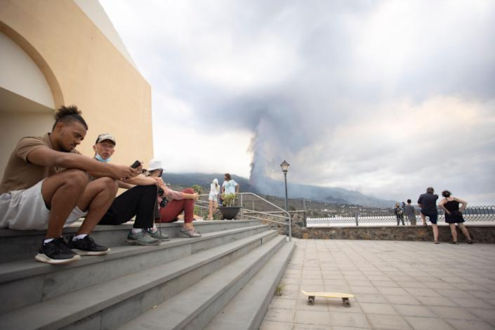 People sit on some steps as others look at the eruption of a volcano near El Paso on the island of La Palma in the Canaries, Spain, Monday, Sept. 20, 2021. Lava continues to flow slowly from a volcano that erupted in Spain's Canary Islands off northwest Africa. Officials say they are not expecting any other eruption and no lives are currently in danger.