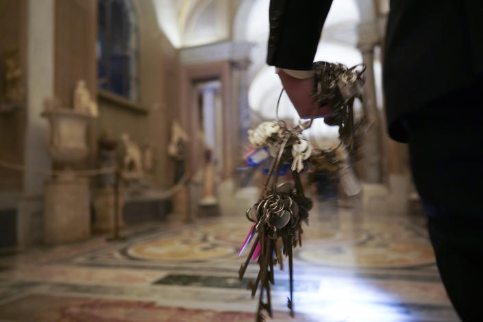 """Gianni Crea, the Vatican Museums chief """"Clavigero"""" key-keeper, holds a bunch of keys as he walks to open the museum's rooms and sections, at the Vatican, Monday, Feb. 1, 2021. Crea is the """"clavigero"""" of the Vatican Museums, the chief key-keeper whose job begins each morning at 5 a.m., opening the doors and turning on the lights through 7 kilometers of one of the world's greatest collections of art and antiquities. The Associated Press followed Crea on his rounds the first day the museum reopened to the public, joining him in the underground """"bunker"""" where the 2,797 keys to the Vatican treasures are kept in wall safes overnight. (AP Photo/Andrew Medichini)"""