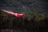 A firefighting plane disperses fire retardant as it assists in extinguishing a fire near the Israeli village of Givat Yearim