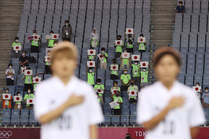 A few people in the stands hold up Japanese flag placards at the Tokyo Olympics.