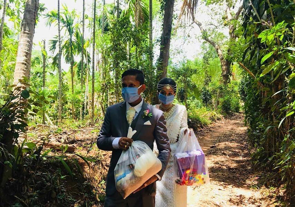 FILE - In this April 27, 2020, photo, Darshana Kumara Wijenarayana and his bride Pawani Rasanga walk with packets of food to distribute in the small town of Malimbada, about 160 kilometers (99 miles) south of the capital Colombo. The Sri Lankan couple cancelled a wedding party and instead, shared their wedding day with some of their neediest neighbors who have been economically hit due to the lock down following the new Coronavirus. (Darshana Kumara Wijenarayana via AP, File)