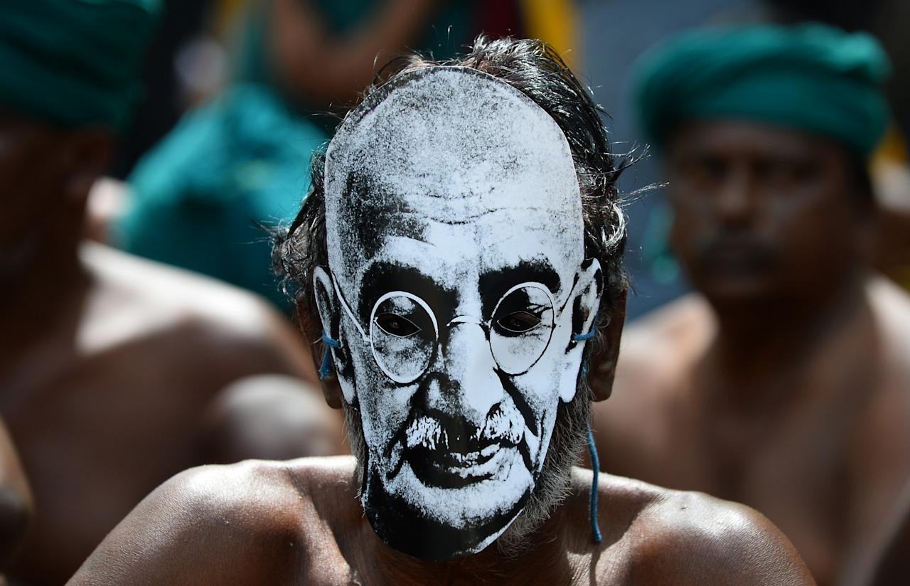 <p>An Indian farmer from the southern state of Tamil Nadu wears a mask with the image of Indian independence icon Mahatma Gandhi on a foothpath as he takes part in a protest in New Delhi on March 26, 2017. Tamil Nadu state farmers are protesting as they demand profitable prices for their agricultral products, and called for the formation of a management committee to solve the Cauvery River water dispute between Tamil Nadu and neighbouring Karnataka. More than 200 farmers have committed suicide in Tamil Nadu in recent months following crop failure due to poor rainfall and inadequate water for irrigation.<br />SAJJAD HUSSAIN / AFP </p>