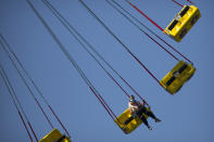 A woman wearing a face mask to protect against the coronavirus rides an amusement park ride at a public park in Beijing, Saturday, Oct. 24, 2020. With the outbreak of COVID-19 largely under control within China's borders, the routines of normal daily life have begun to return for its citizens. (AP Photo/Mark Schiefelbein)