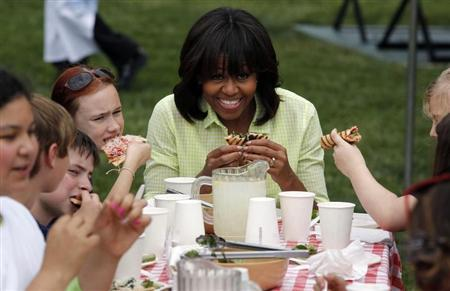 First lady Michelle Obama eats after harvesting vegetables from the summer crop from the White House Kitchen Garden in Washington