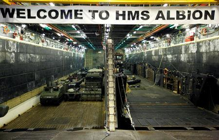 FILE PHOTO: Military vehicles are seen in the loading dock of the HMS Albion, the British Royal Navy flagship amphibious assault ship, after the ship's arrival at Harumi Pier in Tokyo