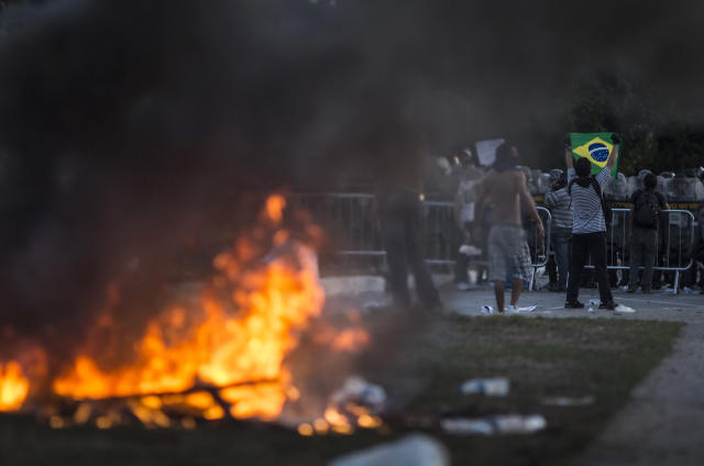 A man holds a brazilian flag near a burning barricade during a protest outside the Minerao stadium during a soccer Confederations Cup match between Japan and Mexico in Belo Horizonte, Brazil, Saturday, June 22, 2013. Thousands of anti-government demonstrators again took to streets in several Brazilian cities Saturday after the president broke a long silence to promise reforms, but the early protests were smaller than those of recent days and with only scattered reports of violence.(AP Photo/Felipe Dana)