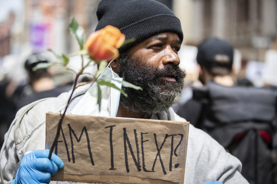"""A man on cheering on the protesters as they make their way down Broadway Street holds a flower and a sign that says, """"Am I Next""""? Photographed in the Manhattan Borough of New York on June 02, 2020, USA. (Photo by Ira L. Black/Corbis via Getty Images)"""