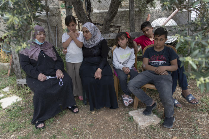 Family members of Palestinian Osama Mansour, who was shot to death by Israeli soldiers at a temporary checkpoint in the occupied West Bank earlier this month, pose for a photo, at their family house, in the West Bank village of Biddu, west of Ramallah, Tuesday, April 20, 2021. Somaya, who was in the car with her husband and was wounded by the gunfire, says they followed the soldiers' instructions and posed no threat. The shooting death has revived criticism of the Israeli military's use of deadly force. (AP Photo/Nasser Nasser)