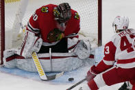 Chicago Blackhawks goalie Malcolm Subban, left, makes a save on a shot by Detroit Red Wings left wing Darren Helm, right, during the second period of an NHL hockey game in Chicago, Saturday, Feb. 27, 2021. (AP Photo/Nam Y. Huh)