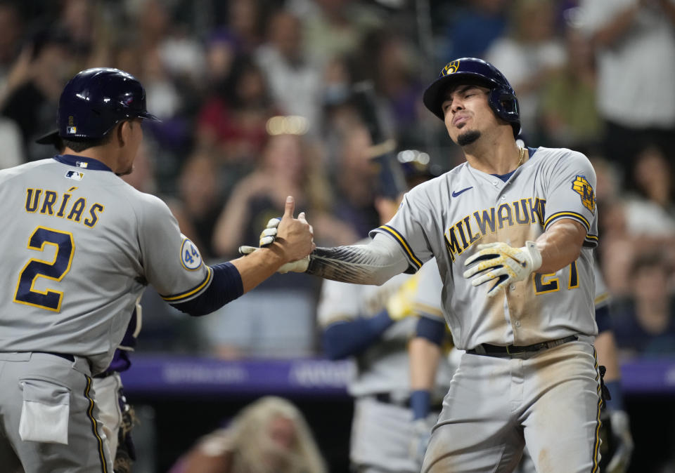 Milwaukee Brewers' Luis Urias, left, congratulates Willy Adames, who crosses home plate after hitting a two-run home run off Colorado Rockies relief pitcher Tyler Kinley during the ninth inning of a baseball game Saturday, June 19, 2021, in Denver. (AP Photo/David Zalubowski)