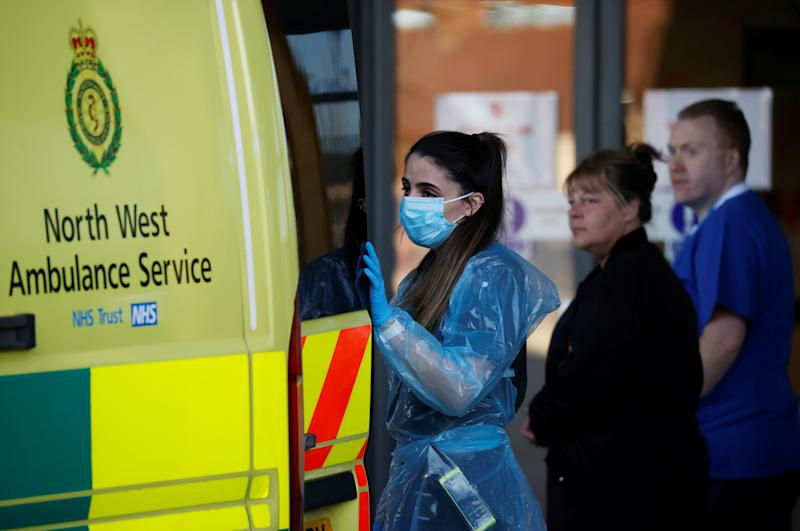 An NHS worker wearing a protective face mask opens an ambulance during the Clap for our Carers campaign in support of the NHS, following the outbreak of the coronavirus disease (COVID-19), Liverpool, Britain, May 14, 2020. REUTERS/Phil Noble