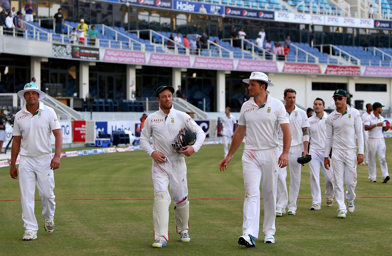 (From LtoR) Jacques Kallis, wicketkkeeper AB de Villiers and captain Graeme Smith of South Africa walk out of the grounds with their team after winning the second test cricket match against Pakistan in Dubai on October 26, 2013. AFP PHOTO/MARWAN NAAMANI        (Photo credit should read MARWAN NAAMANI/AFP/Getty Images)