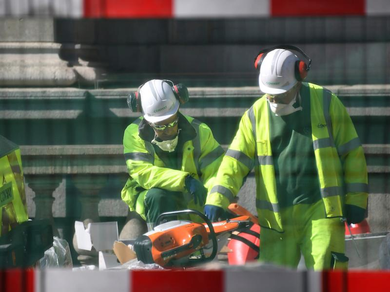 """Construction workers wearing face masks seen through safety fencing work near London Bridge in London, Tuesday, March 24, 2020. Britain's Prime Minister Boris Johnson on Monday imposed its most draconian peacetime restrictions due to the spread of the coronavirus on businesses and gatherings, health workers begged for more gear, saying they felt like """"cannon fodder."""" For most people, the new coronavirus causes only mild or moderate symptoms. For some it can cause more severe illness. (AP Photo/Alberto Pezzali)"""