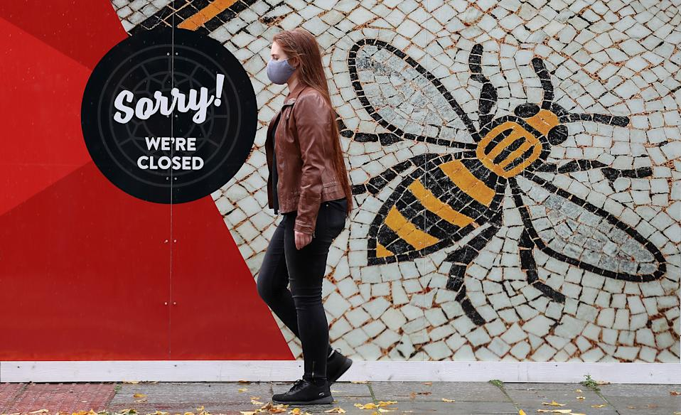 A person wearing a face mask walks past a poster of the Manchester Bee in Albert Square, Manchester as the Government is preparing to impose stringent new coronavirus controls on 2.8 million people after talks with the local leaders for Greater Manchester failed to reach agreement. Leaders have been given until midday on Tuesday to reach a deal, or face unilateral Government action, after 10 days of negotiations failed to reach an agreement.