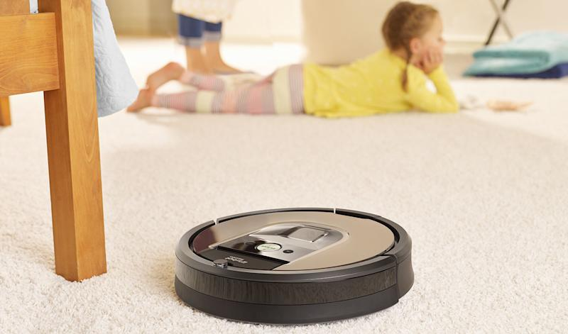 Roomba next to a chair leg, with a child on the carpet in the background.