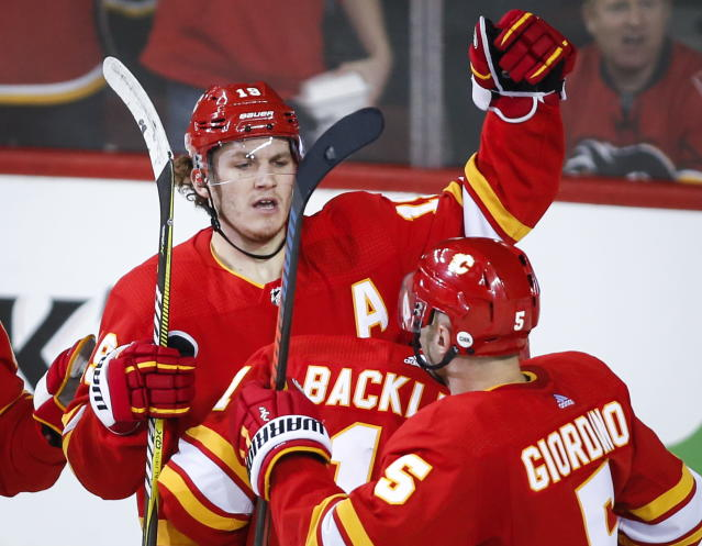 Calgary Flames' Matthew Tkachuk, left, celebrates his goal with teammates during the second period of an NHL hockey game against the New York Rangers in Calgary, Alberta, Friday, March 15, 2019. (Jeff McIntosh/The Canadian Press via AP)