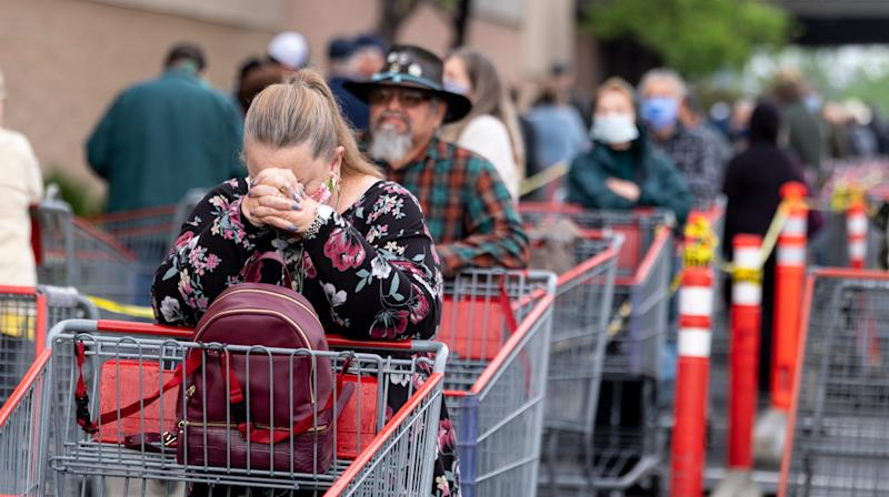 Shoppers, spaced by the width of a parking stall, wait between rows of shopping carts at Visalia Costco on Wednesday, April 8, 2020.