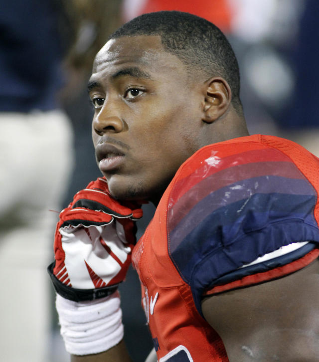 FILE - In this Nov. 9, 2013 file photo, Arizona's Ka'Deem Carey watches from the bench during a game against UCLA, in Tucson, Ariz. Carey will forgo his final season of college eligibility and enter the NFL draft. Carey revealed his decision in an announcement issued by the university. (AP Photo/John Miller, File)