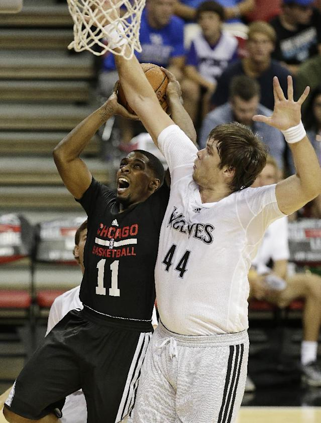 Chicago Bulls' Lazeric Jones (11) goes up for a shot against the Minnesota Timberwolves' Kyrylo Fesenko (44) during the first half of an NBA summer league basketball game Tuesday, July 15, 2014, in Las Vegas. (AP Photo/John Locher)