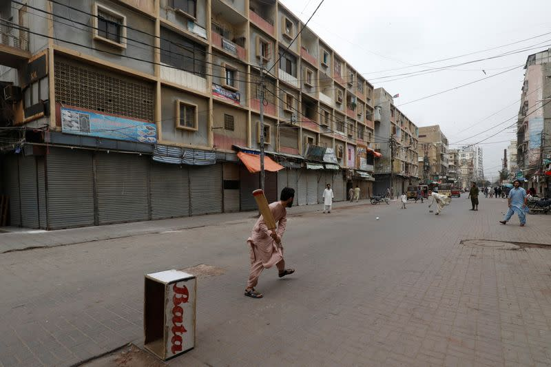 Shopkeepers play cricket along closed market during a partial lockdown amid the outbreak of the coronavirus disease (COVID-19), in Karachi,