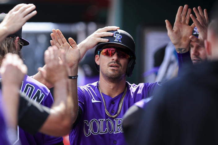 Colorado Rockies' Joshua Fuentes celebrates with teammates after scoring a run during the second inning of a baseball game against the Cincinnati Reds in Cincinnati, Saturday, June 12, 2021. (AP Photo/Aaron Doster)