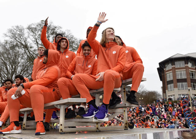 Clemson quarterback Trevor Lawrence, right, along with fellow freshman ride in the parade honoring Clemson Saturday, Jan. 12, 2019, in Clemson, S.C., Clemson defeated Alabama 44-16 in the College Football Playoff championship game Monday Jan. 7. (AP Photo/Richard Shiro)