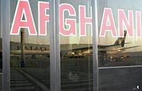 A Qatar Airways aircraft is reflected on the windowpanes of a shuttle bus carrying passengers to board the flight at the airport in Kabul on September 9, 2021 (AFP/WAKIL KOHSAR)