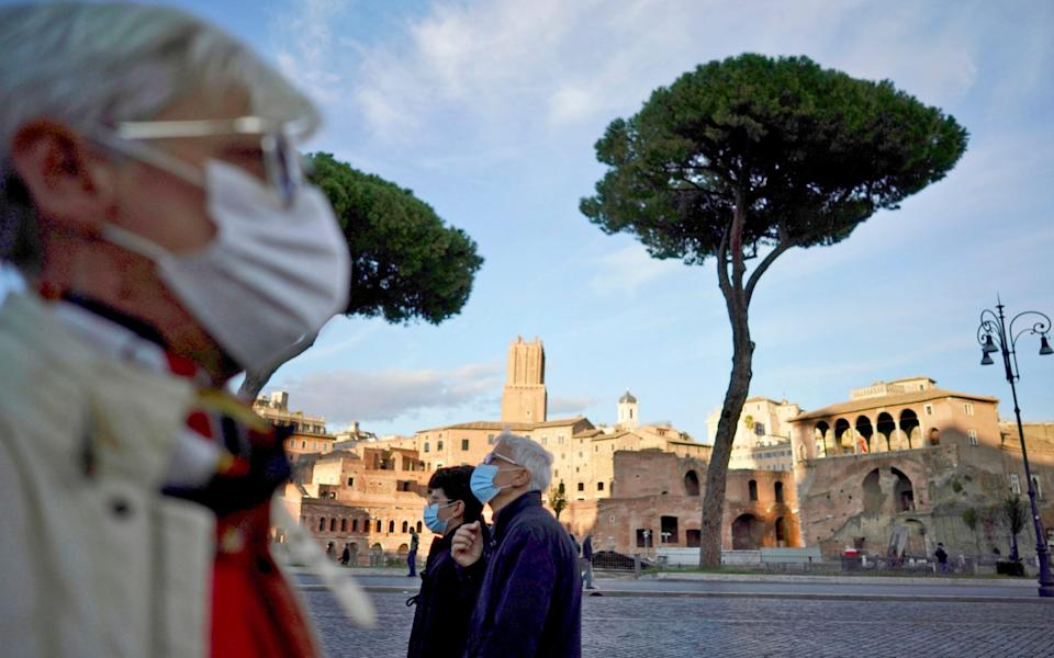People wear masks outside in Rome following the introduction of new rules - AP