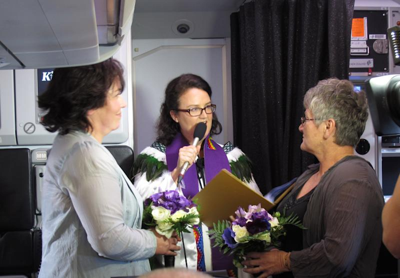 Lynley Bendall, left, and Ally Wanikau, right, are married by celebrant Kim Jewel Elliott Monday, Aug. 19, 2013, on a flight that left from Queenstown, New Zealand. A law change allowed same-sex couples to marry in New Zealand for the first time Monday. The couple celebrated the legalization of gay marriage in New Zealand by getting hitched in a plane at 39,000 feet (11,900 meters). Bendall and Wanikau celebrated their wedding in the air after they won a promotion by national carrier Air New Zealand. (AP Photo/Nick Perry)