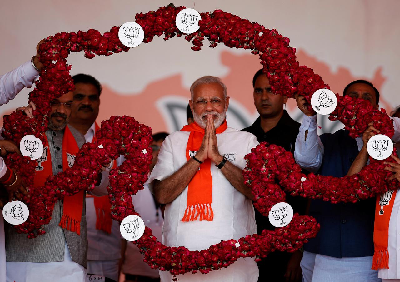 India's Prime Minister Narendra Modi is garlanded by supporters during a public rally at Bhaat village on the outskirts of Ahmedabad, India October 16, 2017. REUTERS/Amit Dave     TPX IMAGES OF THE DAY